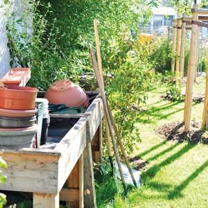 Arbeitstisch im Garten des Matthias Claudius Haus. Auf dem Tisch stehen rote Tontöpfe.