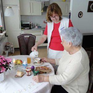Eine Pflegekraft serviert Frühstück.