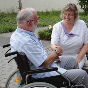 Pflegekraft begrüsst lächelnd einen alten Mann im Rollstuhl.