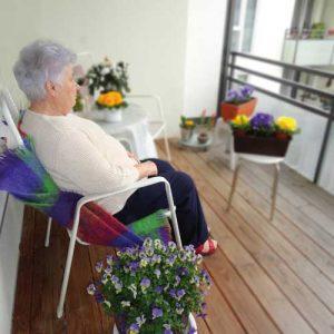 Eien alte Frau sitzt im Gartensessel auf dem Balkon.